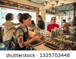 young female bartender standing ... | Shutterstock . vector #1335703448