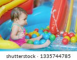 little baby girl in colorful... | Shutterstock . vector #1335744785