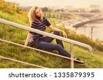 young fashion woman sitting on...   Shutterstock . vector #1335879395