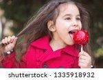 adorable little girl eating red ... | Shutterstock . vector #1335918932