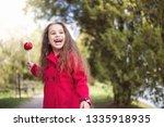 adorable little girl eating red ... | Shutterstock . vector #1335918935
