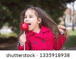 adorable little girl eating red ... | Shutterstock . vector #1335918938