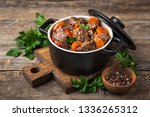 Small photo of beef stew with vegetables in black pot on dark wooden background, selective focus