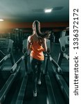 Small photo of Slim brunette in orange sportswear and ponytail running on treadmill in gym at night. Backs turned. Do it now, sometimes later becomes never.