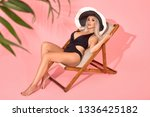 Young woman in black swimsuit relaxing on chaise longue, studio shot. Blurred palm tree leaves in foreground.