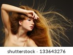 portrait of young beautiful redhead woman with waving long curly hair on gray - stock photo