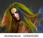 portrait of young beautiful redhead woman with long hair colored with green red and blue - stock photo