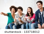 Small photo of Happy Group Of Young Friends Playing Video Games At Home