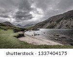 Grey, moody and dark cloudy sky above majestic valley with lake and mountain peaks in background.Beautiful landscape of Lake District National Park in Cumbria, North West England.