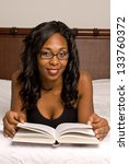 African American woman laying down and reading - stock photo