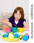 Young girl in the process of coloring Easter Eggs - Step five, the egg completely submerged in the cup of dye - stock photo