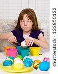 Young girl in the process of coloring Easter Eggs - Step one, placing the egg on a spoon - stock photo