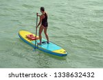 young woman paddle boarder | Shutterstock . vector #1338632432