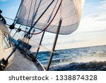 white yacht sailing at sunset.... | Shutterstock . vector #1338874328