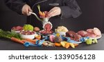 Small photo of Man preparing fresh health barf food for his dog with a selection of fresh vegetables, heart, stomach, offal, organs, poultry and beef processing them through an old meat grinder