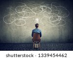 Small photo of Back view of a thoughtful young businessman sitting on chair looking at a scribble on a wall feeling confused with too many questions
