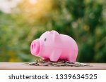 happy piggy bank and coins over ... | Shutterstock . vector #1339634525