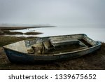 Small photo of A boat lies, decrepit on a misty beach