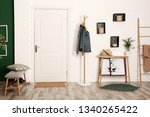 Stylish hallway interior with shoe storage bench, hanger stand and table