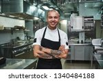 Small photo of I love my work Cheerful young chef in apron keeping tattooed arms crossed and smiling while standing in a restaurant kitchen