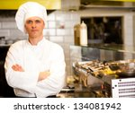 Handsome and confident young male chef, kitchen background. - stock photo