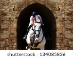 White horse with a equestrian jump on the fortress gate's background - stock photo