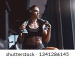 Small photo of Young attractive strong muscular female bodybuilder with ponytail and headphones posing in gym with towel around neck. When life is tough, remember you are tougher.