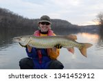 A woman in a drysuit holding a gold and green muskie fish on a river in winter at sunset on a partly cloudy day