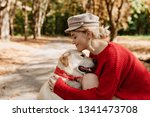 Stock photo young blonde in trendy red clothes smiling at her lovely labrador in autumn park lovely girl and 1341473708
