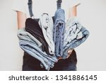 the girl holds a stack of jeans ... | Shutterstock . vector #1341886145