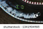 Small photo of Two cars drifting battle on race track with smoke, Aerial view two car drifting battle.
