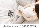pregnant woman making packing... | Shutterstock . vector #1341916205