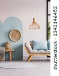 Small photo of Wicker chandelier above wooden Scandinavian sofa with futon in bright living room interior