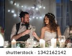 a young couple sitting at a... | Shutterstock . vector #1342162142