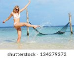woman in bikini splashing in... | Shutterstock . vector #134279372