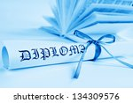 Diploma with blue ribbon and book - stock photo