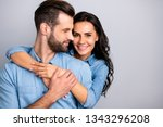Small photo of Love affair. Portrait of charming couple of millennial cheerful positive placing hands around chest wavy curly hair wearing blue denim shirts isolated on grey background