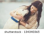 Stock photo portrait of beautiful young woman playing with dog on the sea shore 134340365