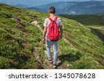 Small photo of Traveler man with a red backpack, guy lost in mountains walking along path, Boy spring summer walk back in nature, hiking in forest on top, trail, equipment for tourism and sports, afoot lifestyle