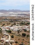Bird's eye view of Nijar, a typical whitewashed Andalusian village in the province of Almeria, Spain, with greenhouses in the background. - stock photo