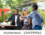 young family sitting in a park... | Shutterstock . vector #1345599062