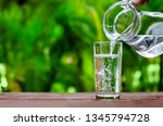 Water in jug poured into glass on wood with nature background. World Water Day