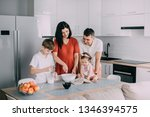 young family preparing food in... | Shutterstock . vector #1346394575