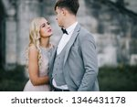 The stylish young bride and groom are expressing their affectionate love to each other. Old abandoned palace is at the background. Parisian styled photos on a sunny day.