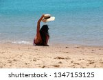 young woman sitting on sandy...   Shutterstock . vector #1347153125