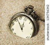 antique clock in the sand   Shutterstock . vector #134756342