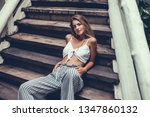 Small photo of Young beautiful girl's white hair, in a tattoo posing outside, hipster style, emotional portrait, leather jacket, dress, brash girl, sunglasses, tattoo, street, USA, rock, bad girl