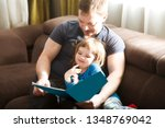 father reading a story to his... | Shutterstock . vector #1348769042