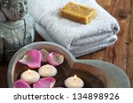stone heart with water rose petals and floating candles and buddha head and towels with soap in the background - stock photo
