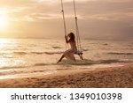 Silhouette Of Woman On Swing...